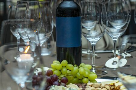 Space to write text. The concept of wine consumption. Wine bottle, a glass with grapes, bunches of grapes. A bottle of wine with space to writing. Banco de Imagens