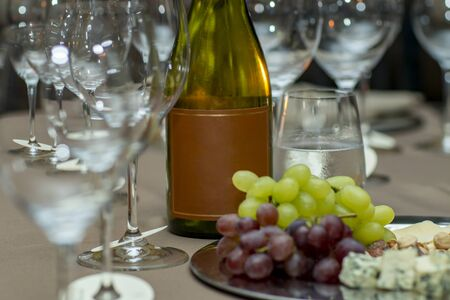 Bouteille de vin et variété de fromages pour le goûter. Espace libre pour le texte.