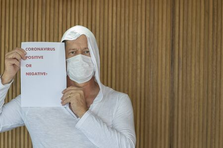 Coronavirus positive or negative? Man with mask and sign against coronavirus. Banque d'images - 144520651