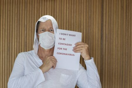 Man with mask and sign against coronavirus. I don't want to be contagious with the coronavirus!