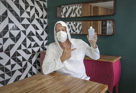 The confident man presenting and showing an antibacterial gel bottle in his hand. A mature man wearing medical mask on his face and holding disinfectant in his hand. Preventive measures against the COVID-19 coronavirus.
