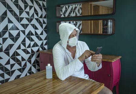 Coronavirus. Man quarantine at home with mobile.