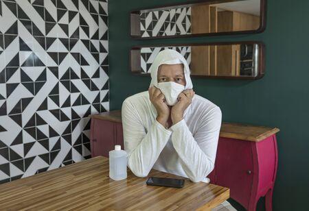 Man with coronavirus. Coronavirus sick man looking at camera wearing a protective mask and recovering from illness at home. Stockfoto