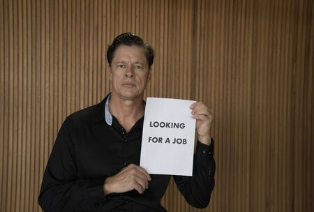 Looking for a job. COVID-19. The unemployed guy with sign LOOKING For A JOB. Unemployment during coronavirus COVID-19 crisis, the concept of job loss.
