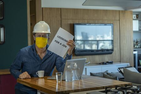 Looking for a job. COVID-19. The unemployed man with sign LOOKING For A JOB. Unemployment during coronavirus COVID-19 crisis, the concept of job loss. Stockfoto