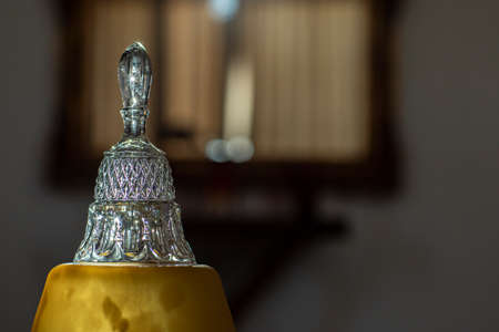 Crystal bell. Blurred background. Glass object.
