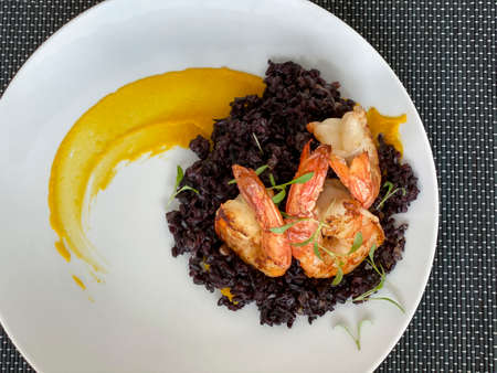 Gourmet food. Shrimp with black rice.