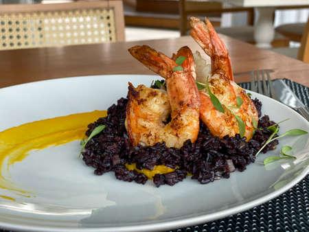Gourmet food. Shrimp with black rice. Imagens - 165878127