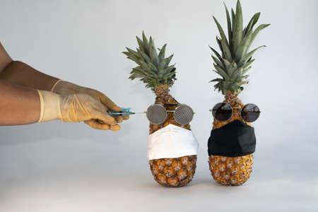 Injection against covid-19. Vaccine syringe in hand to perform the imminent vaccination injection against the covid virus 19 in a pineapple. Imagens - 165878133