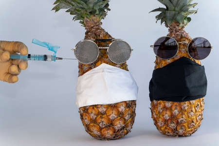 Injection against covid-19. Vaccine syringe in hand to perform the imminent vaccination injection against the covid virus 19 in a pineapple. Imagens - 165878136