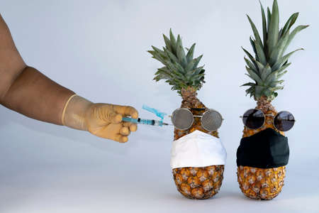 Injection against covid-19. Vaccine syringe in hand to perform the imminent vaccination injection against the covid virus 19 in a pineapple. Imagens - 165878208