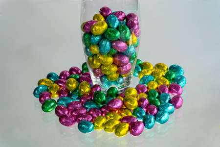Easter celebration concept. Glass vase with chocolate candies.