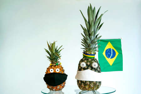 Flags country in fruits. Pineapple with the flag of Brazil and mask against Covid-19.