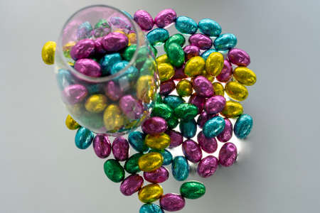 Many colors together. Glass vase with chocolate candies.