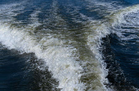 The trail on water surface behind of fast-moving motorboat.