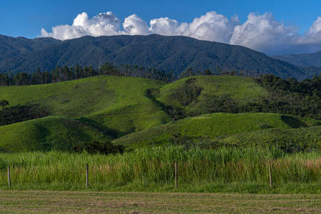 Beautiful view of green hill mountain field with blue sky and clouds background.