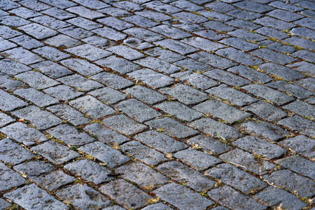 Cobblestone road. Abstract background of old cobblestone pavement close-up.