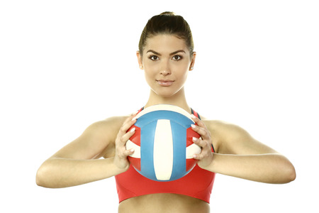 sportingly: beautiful woman with volleyball ball on white background Stock Photo