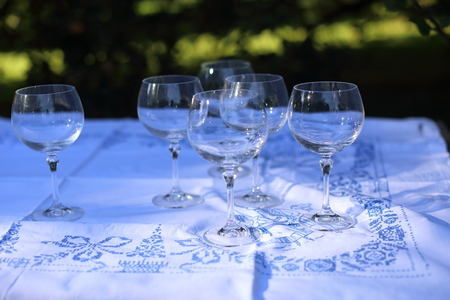 Empty wine glasses aon the white tablecloth in the garden Imagens