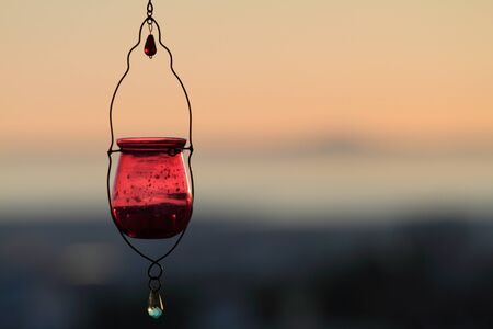 Red candle lamp at dusk against faded background photo