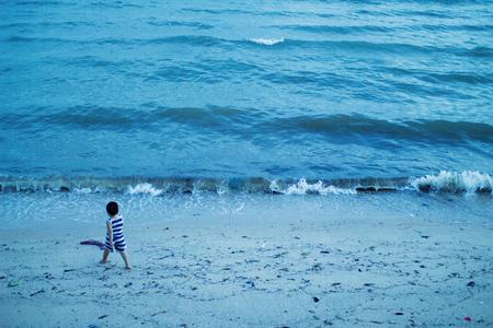 pyjama: boy walking and playing on the beach Stock Photo