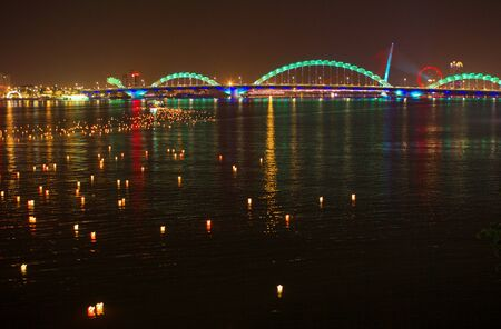 reflections of colourful dragon bridge and candles on river
