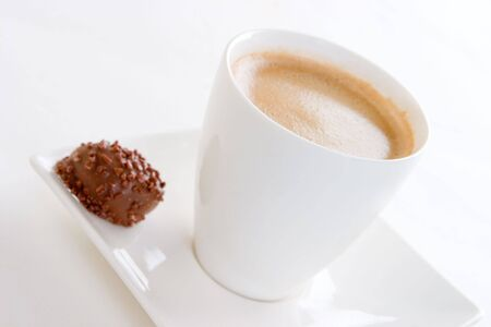 A cup of creamy black coffee on a square saucer with a chocolate, focussed on the coffee cup
