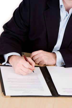 A business man in a blue suit and no tie signing a contract Standard-Bild