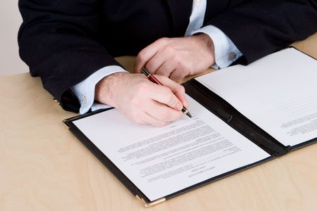 A business man in a blue suit signing a contract on a wooden table