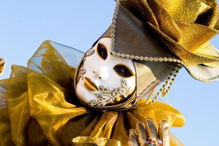 A venetian woman in a gold costume with a white mask
