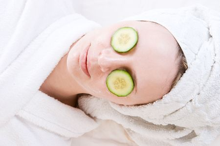 A woman with a facial mask and cucumber on her face