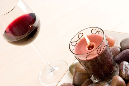 A glass of red wine next to a candle and stones photo