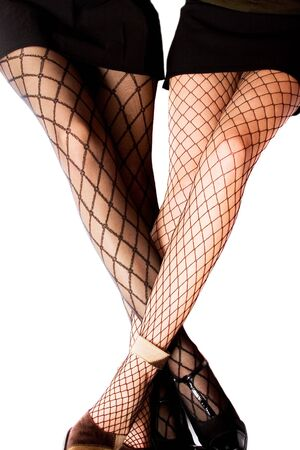 Two women wearing  fishnet tights with crossed legs photo