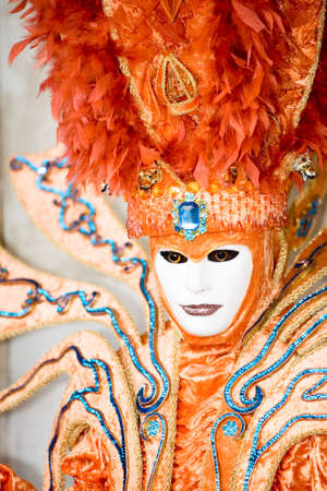 customs and celebrations: An bright orange costume at the Venice Carnival