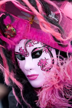 customs and celebrations: Secrative eyes hidden behind a pink venetian mask Stock Photo