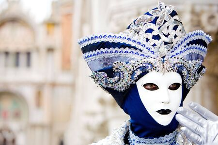 A man in a blue and silver Venetian costume standing in St. Mark's Square, Venice