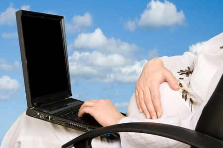 A pregnant lady holding her stomach and typing on a laptop