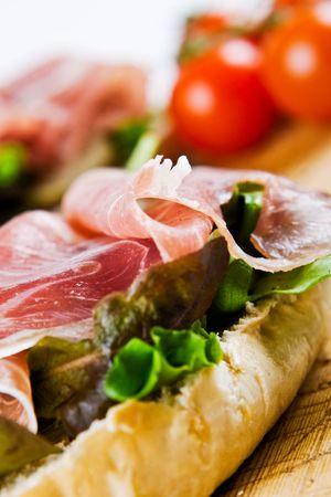 ham sandwich: Primo piano di un panino al prosciutto di Parma con pomodori in background