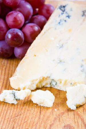stilton: Blue stilton cheese with grapes on a wooden board