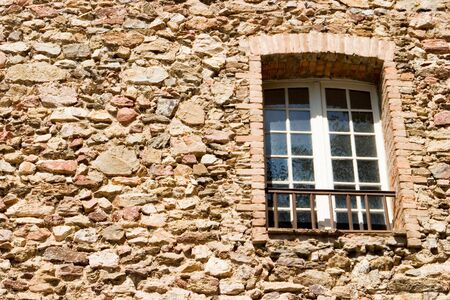 An old stone wall with a window photo