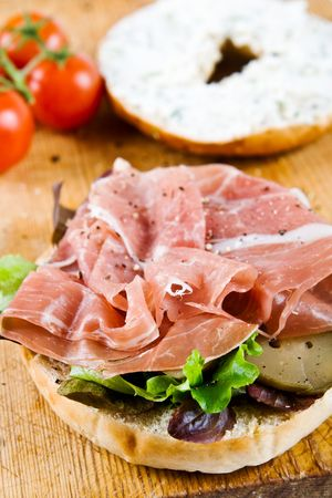 A bagel sandwich with parma ham, cream cheese and tomatoes photo