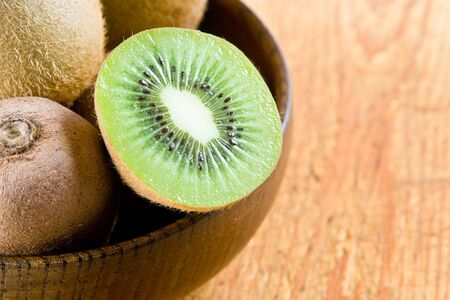 Half a kiwi in a wooden bowl photo