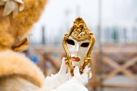 A venetian mask reflected in a mirror photo