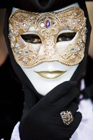 customs and celebrations: Venetian man in black costume with a golden mask Stock Photo