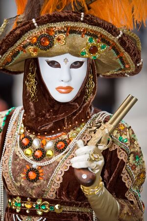 A person in costume holding a pistol at the Venice Carnival photo