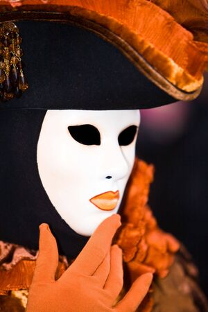 customs and celebrations: Black and orange costume at the Venice Carnival