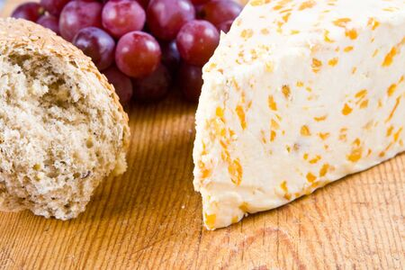 stilton: Apricot stilton cheese with grapes and bread on a wooden board Stock Photo