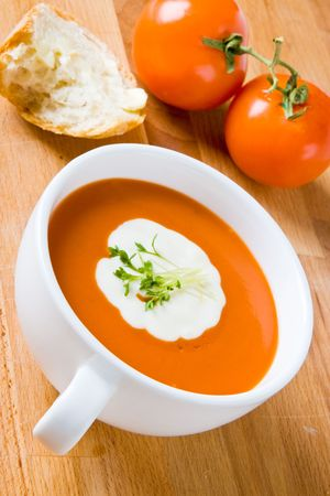Tomato soup with cream, bread and fresh cress photo