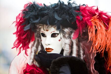 customs and celebrations: Black and red hat with white mask at the Venice Carnival