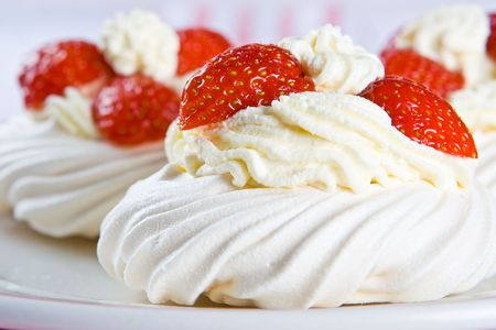 calorie rich food: Fresh meringue with thick cream and strawberries on a plate